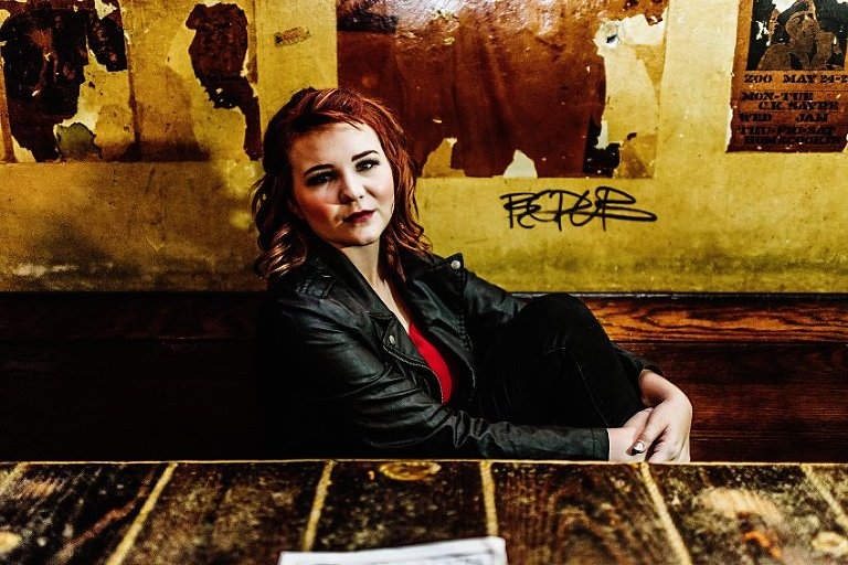 girl in red top and leather jacket sitting in an old booth against the wall with torn posters and graffiti behind her
