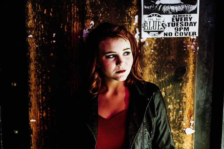 girl in red top and leather jacket standing in front of an old wall with band posters behind her