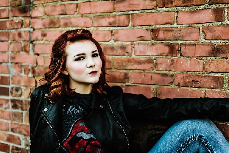 girl in red top and leather jacket sitting in an alley in front of a brick wall