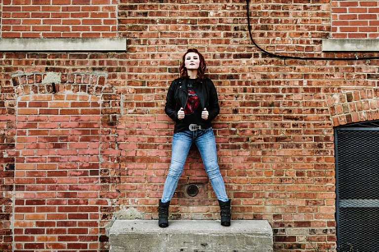 girl in red top and leather jacket standing on a concrete block in an alley in front of a brick wall