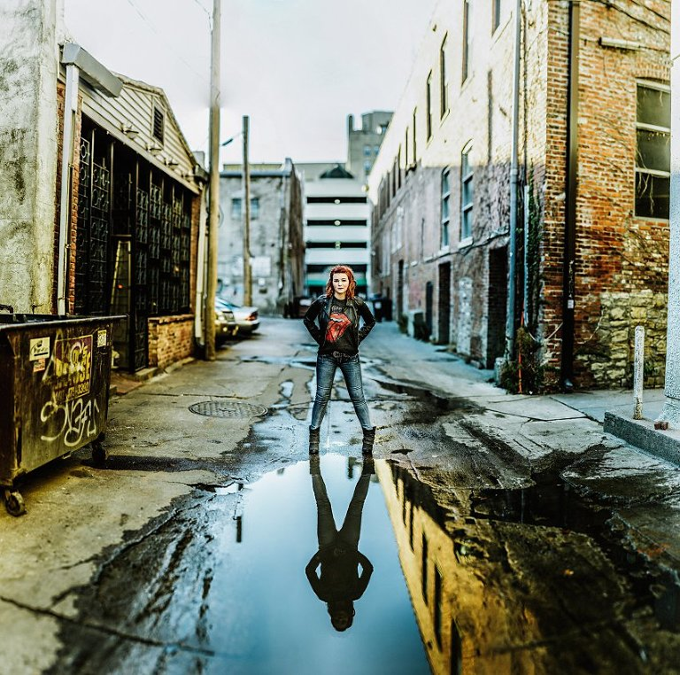 girl in red top and leather jacket standing in an alley in front of her reflection in a pool of water