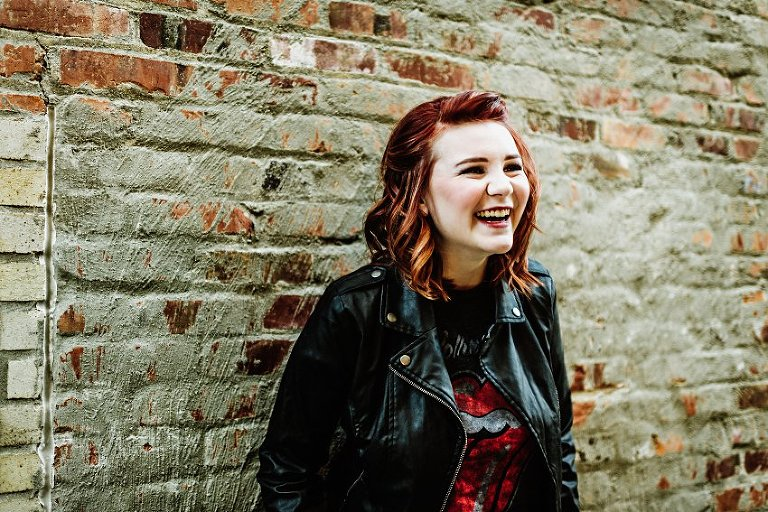 girl in red top and leather jacket in front of a brick wall laughing