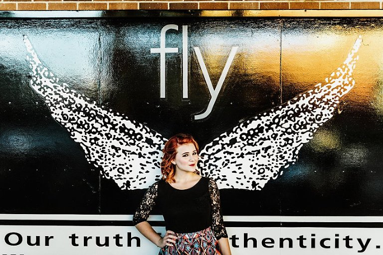 girl in a black top and colorful patterned skirt standing in front of a big poster with wings and the word fly