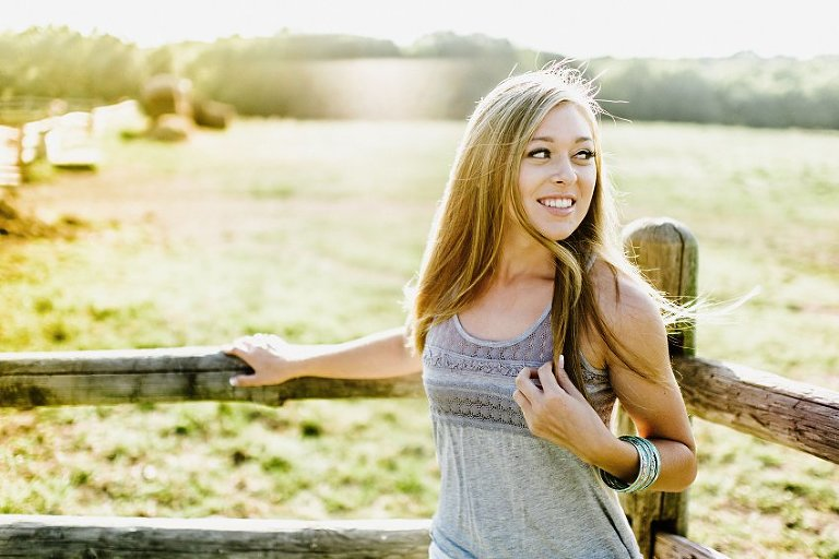 girl in a gray tank top standing by a fence and open field in sunset