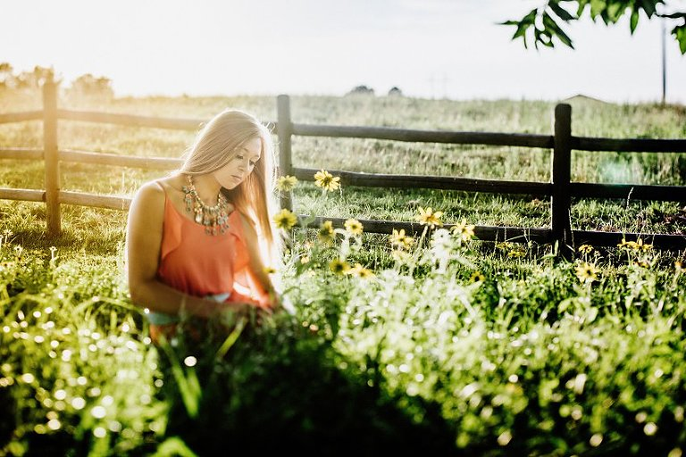 girl in a pink dress in a hazy sunset sitting in tall grass