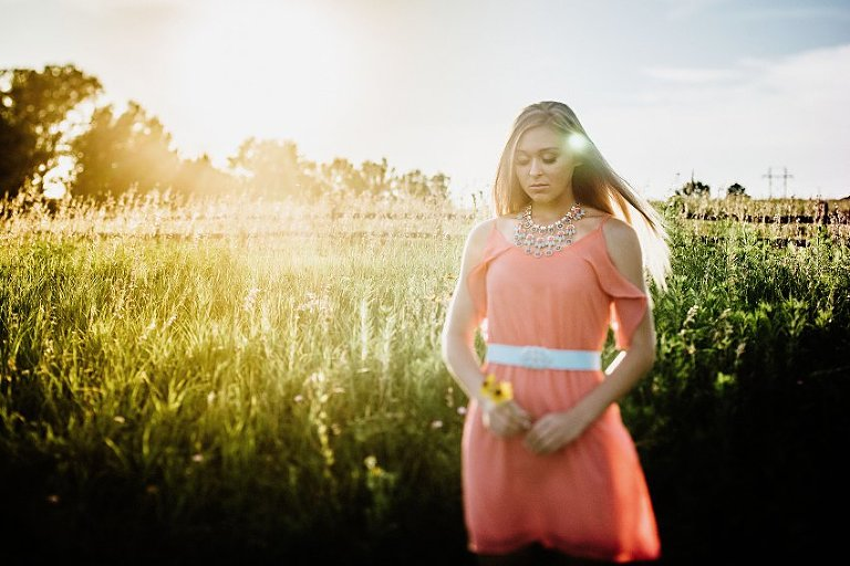 girl in a pink dress in a hazy sunset walking in tall grass