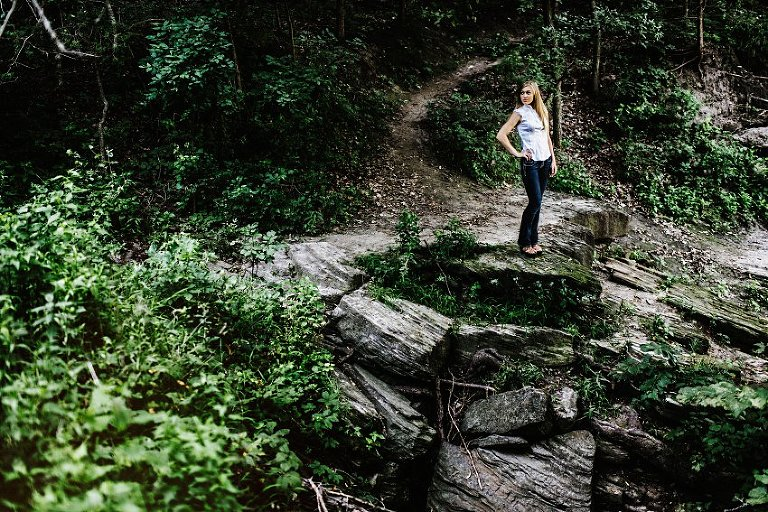 girl in a white top and black pants standing on a rocky ledge in the woods