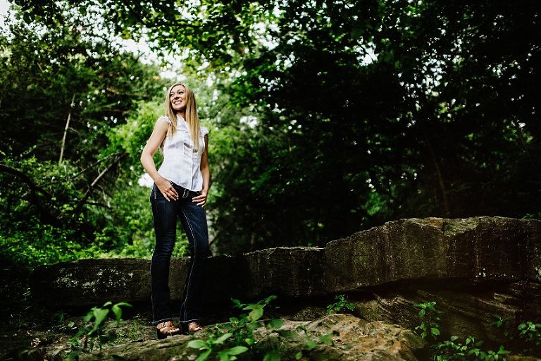 looking up at girl in a white top and black jeans standing on a rocky ledge