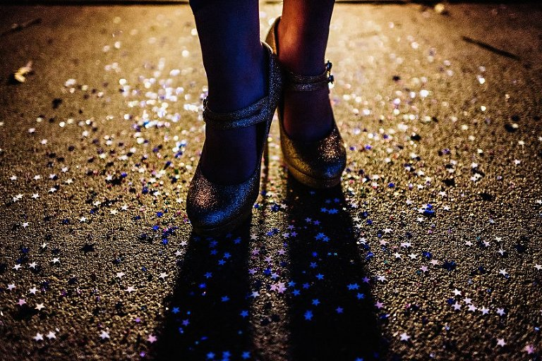 sparkly high heels lit from the back standing in glitter