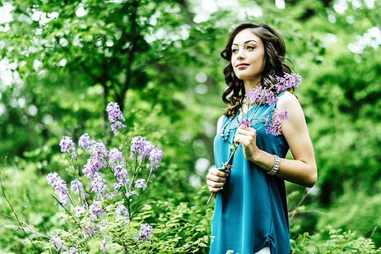 girl in white pants and a blue top holding flowers and looking off camera