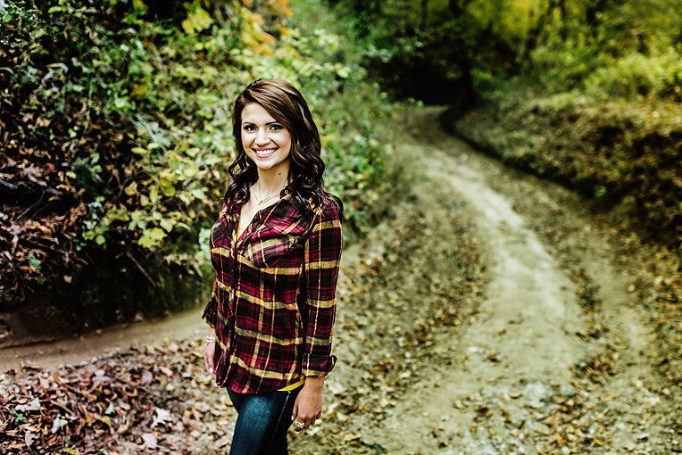 girl in a flannel standing on a path in the woods in the fall