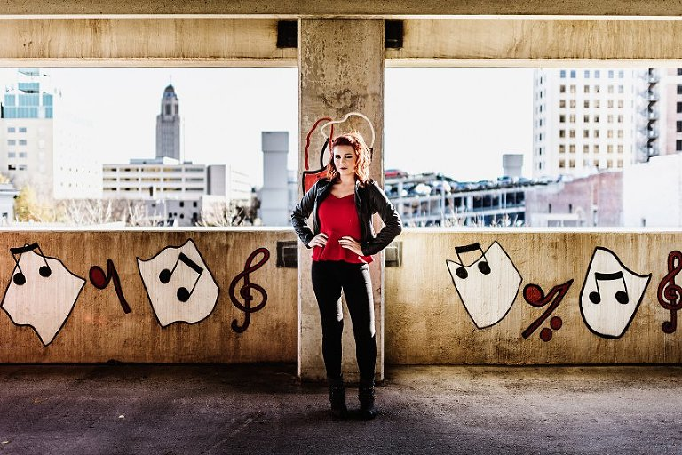 girl in red top and leather jacket standing in a parking garage with music graffiti in the background