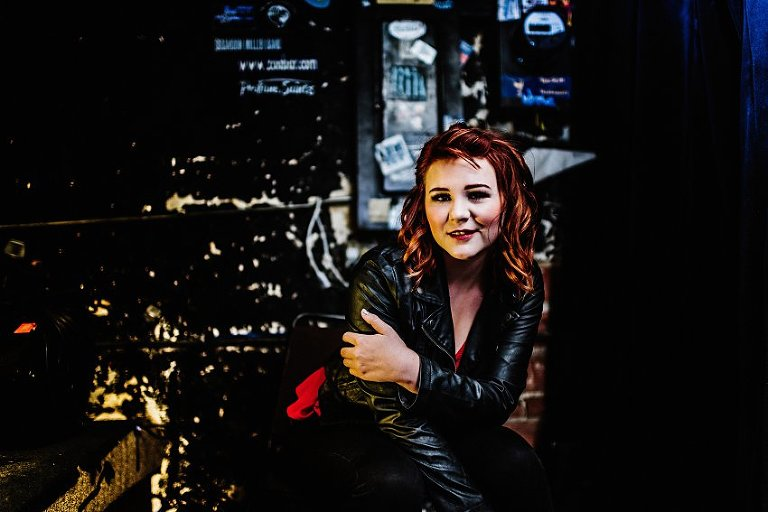 girl in red top and leather jacket sitting in front of an old wall