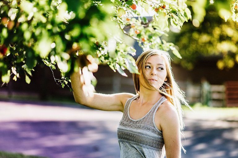 girl in a gray top standing under a crab apple tree